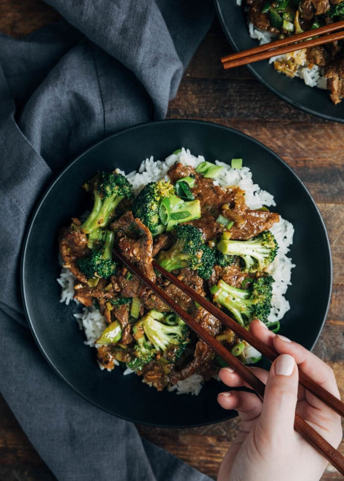 overhead of Beef and Broccoli over rice being eaten with chopsticks