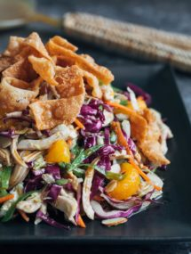 chinese chicken salad with crispy wonton strips on a black plate