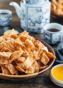 crispy fried wonton strips in a bowl with duck sauce and cups of tea