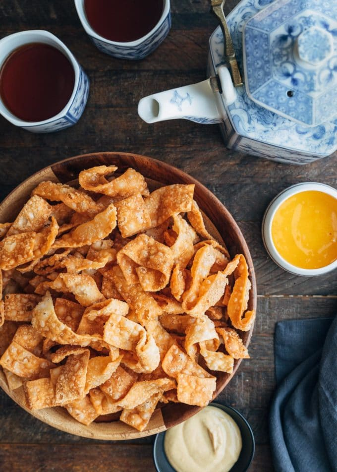 overhead view of crispy wonton strips with dipping sauces and cups of tea
