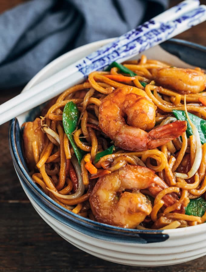shrimp lo mein in a ceramic bowl with white chopsticks