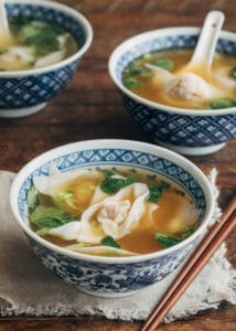 wonton soup in blue floral printed bowls with wooden chopsticks
