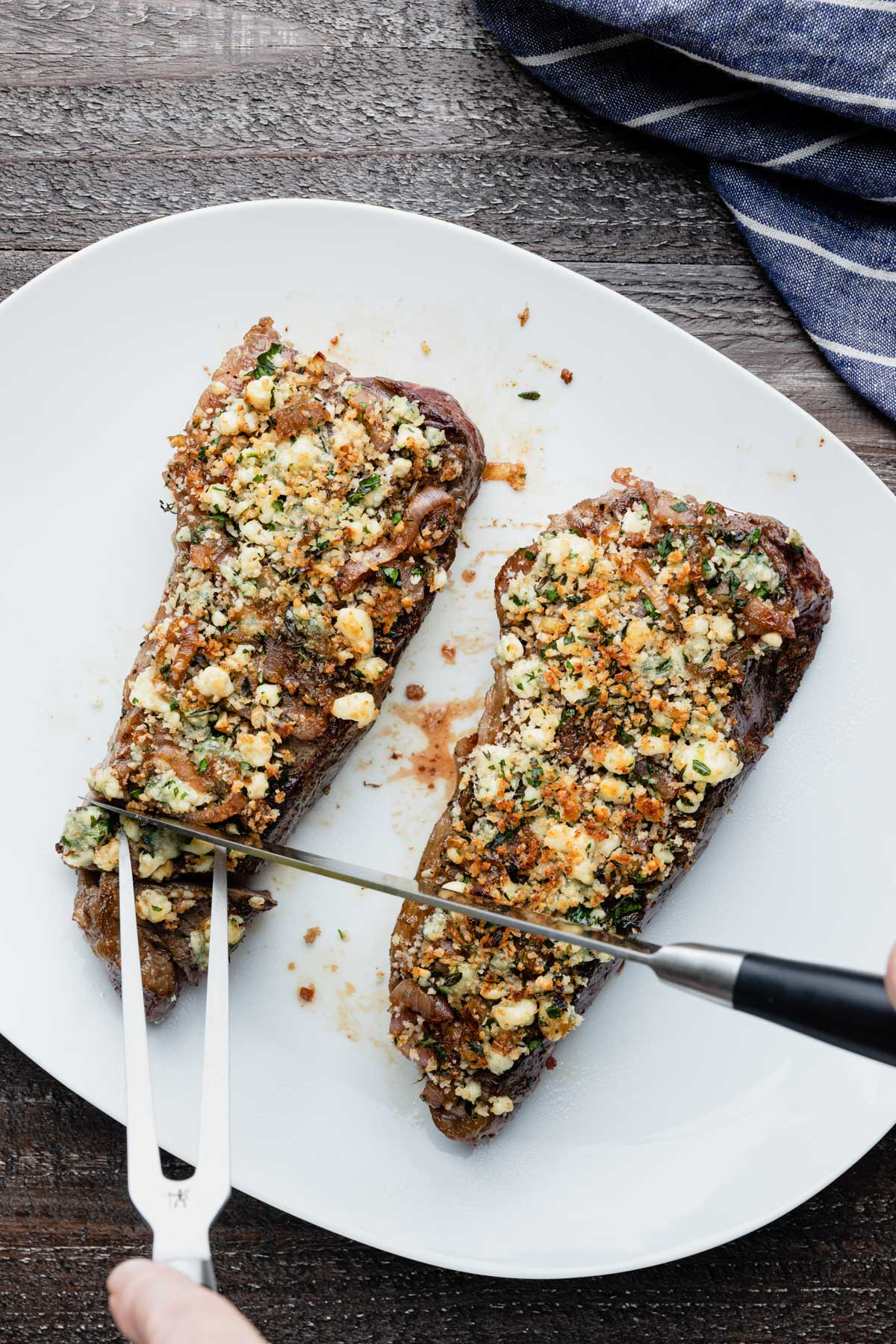 slicing blue cheese crusted steak on a white serving platter