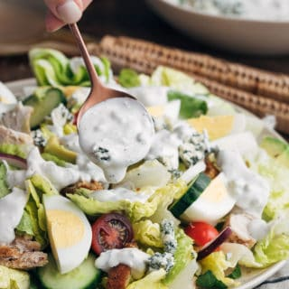 homemade blue cheese dressing being drizzled over a house salad