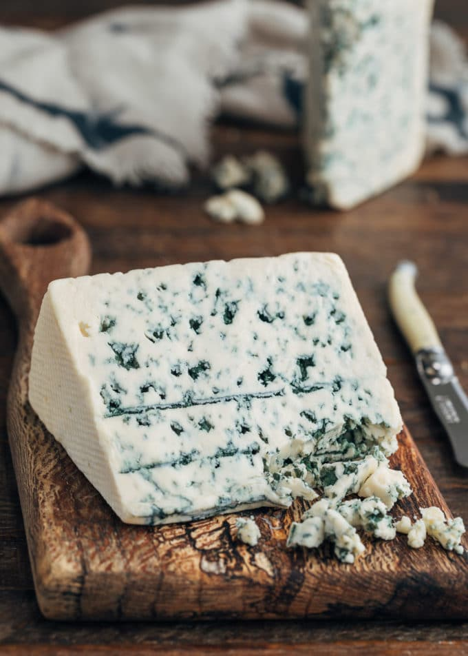 wedge of Danish blue cheese on a wood board