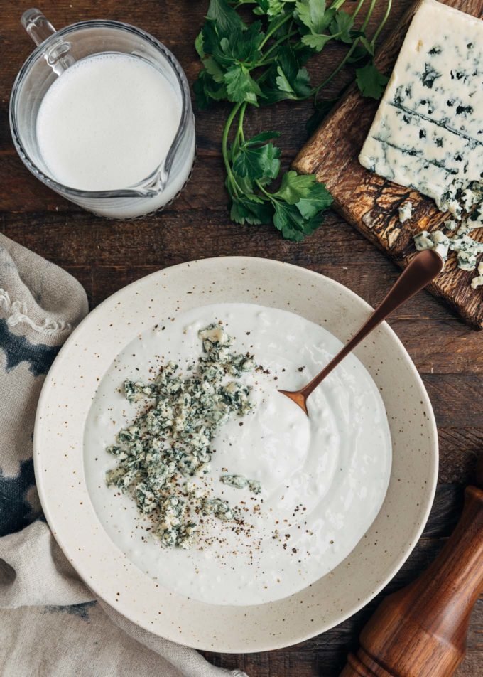 crumbled blue cheese on top of a bowl of blue cheese dressing