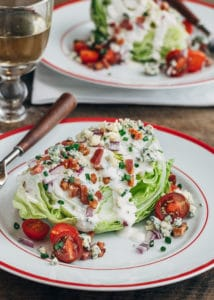 classic wedge salad with iceberg lettuce, bacon, and blue cheese dressing on a plate