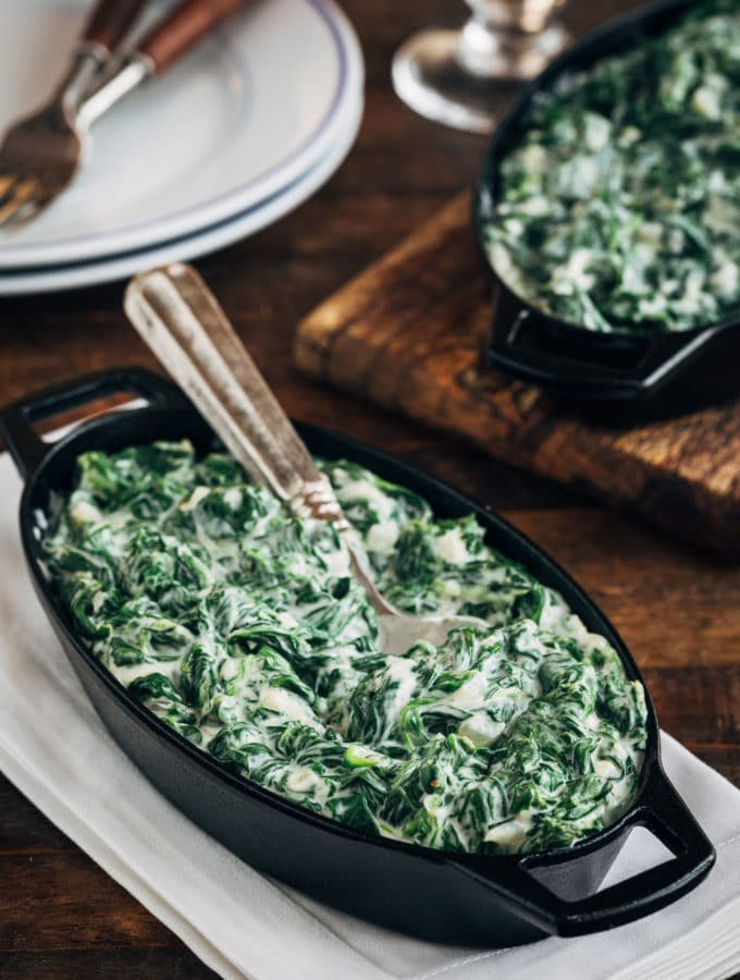 creamed spinach in a cast iron gratin with a spoon