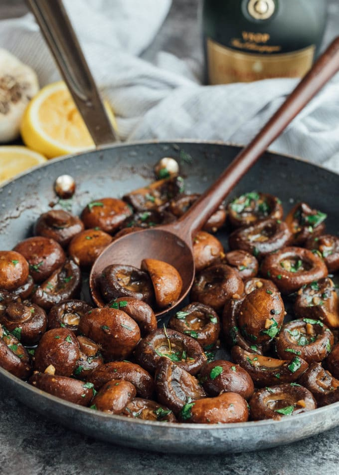 sauteed mushrooms in a skillet with parsley