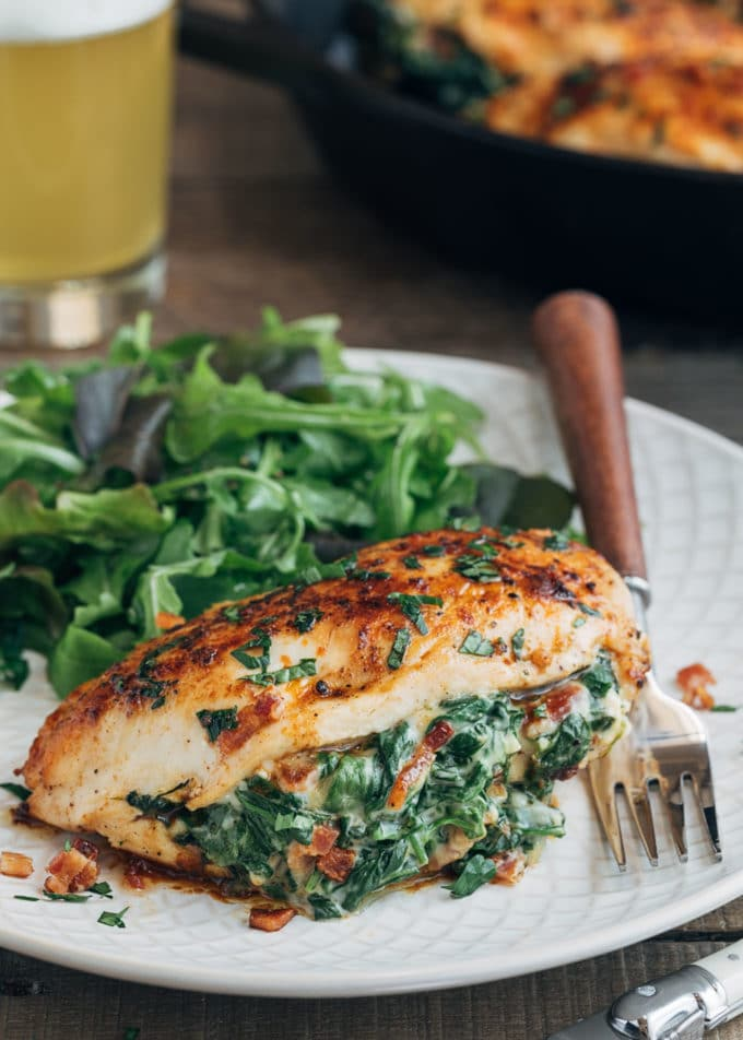 spinach stuffed chicken breast on an ivory plate with salad greens