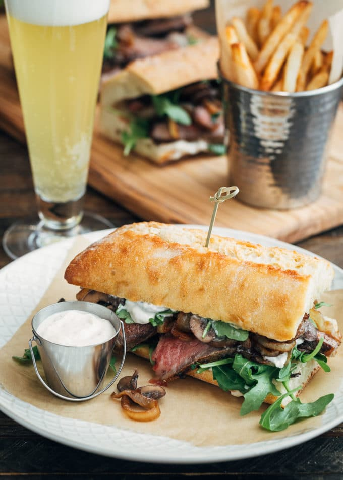 steak sandwich served with horseradish mayo, french fries, and beer