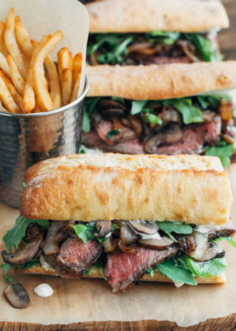 steak sandwiches with horseradish mayo on a wood board