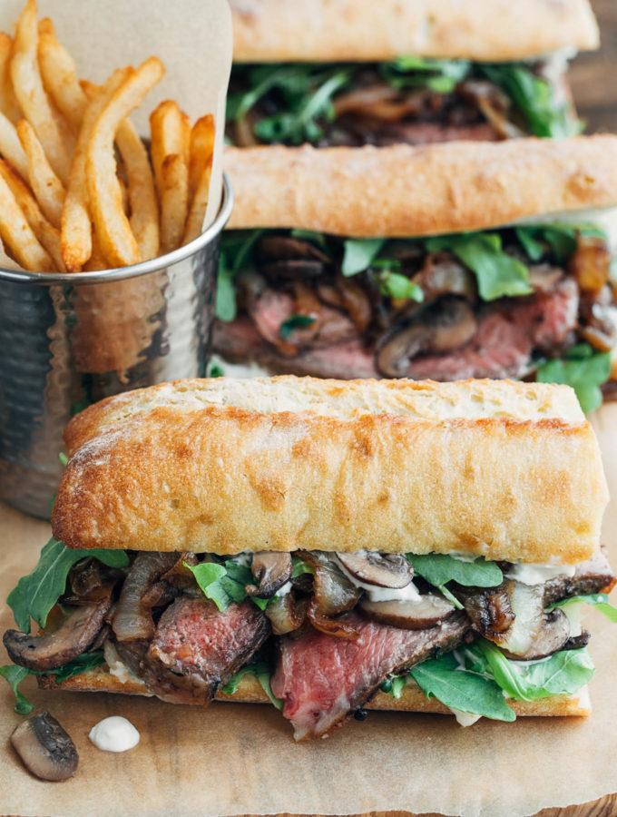 steak sandwiches with horseradish mayo on a wood board