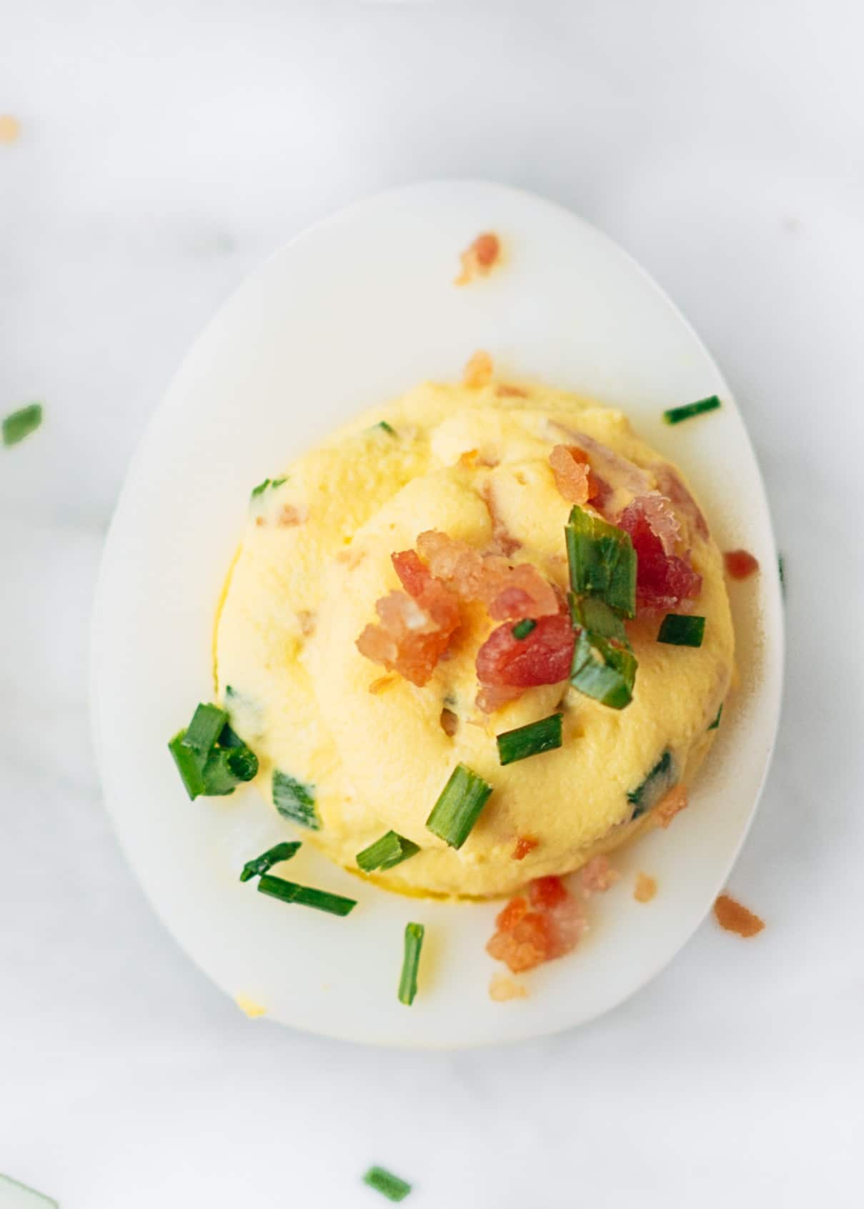 bacon deviled egg with horseradish and chives on a marble board