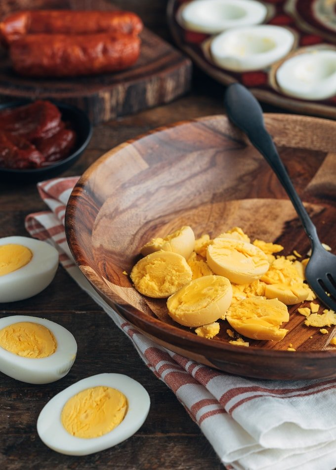 hard boiled egg yolks in a wooden bowl and halved hard cooked eggs