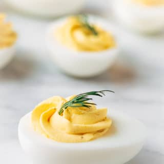 classic deviled eggs with dill on a marble board