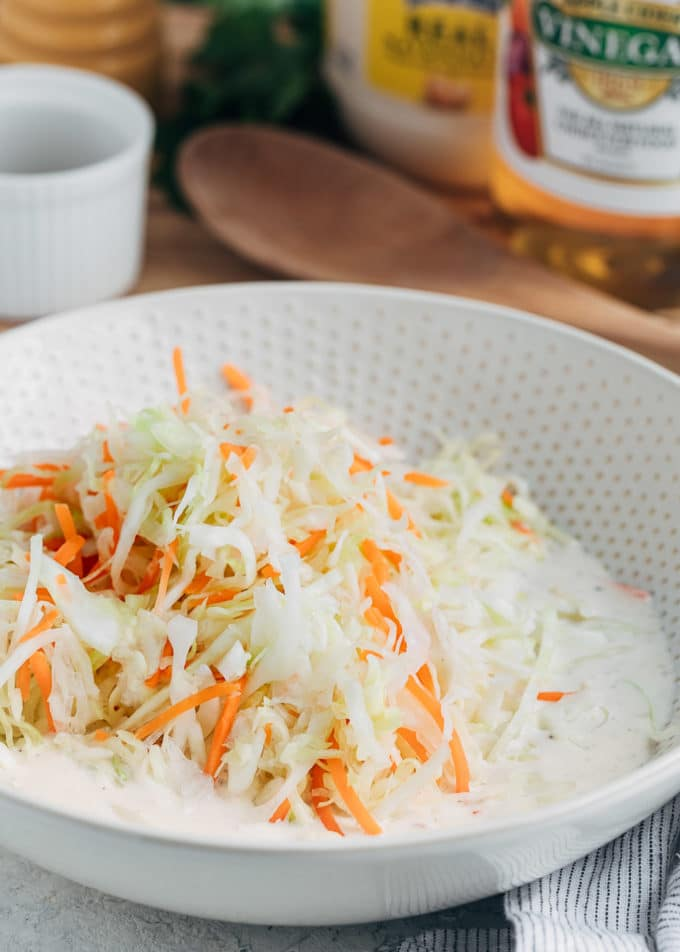 shredded cabbage and carrots in coleslaw dressing in a bowl