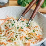 homemade coleslaw in a bowl with wooden serving spoons