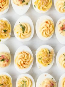 overhead view of garnished deviled eggs on a white board