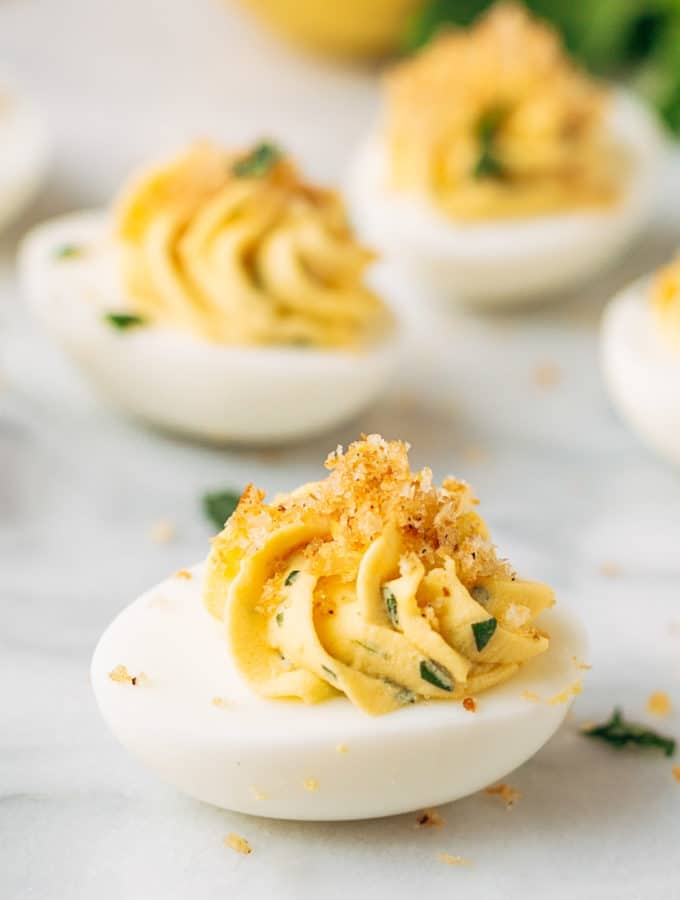 Italian deviled eggs on a white marble board