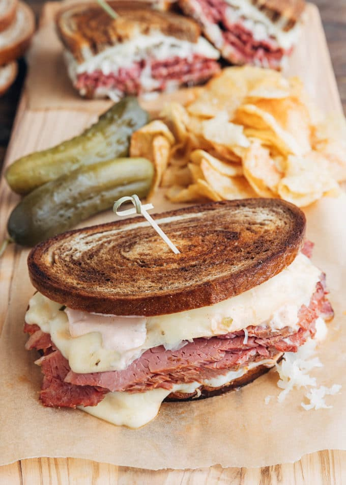 reuben sandwich on a board with chips and pickles
