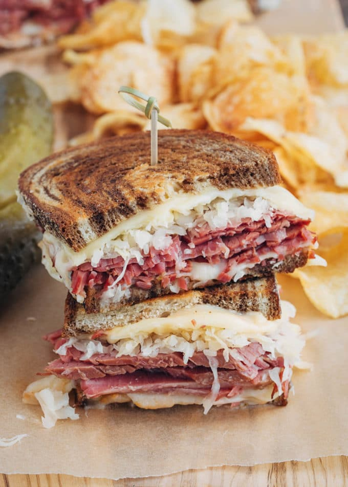 stacked halves of a grilled reuben sandwich with potato chips