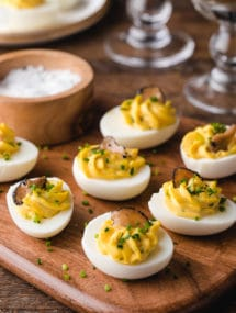 truffled deviled eggs with chives on a wood board