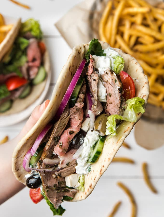 closeup of a hand holding a roasted lamb pita