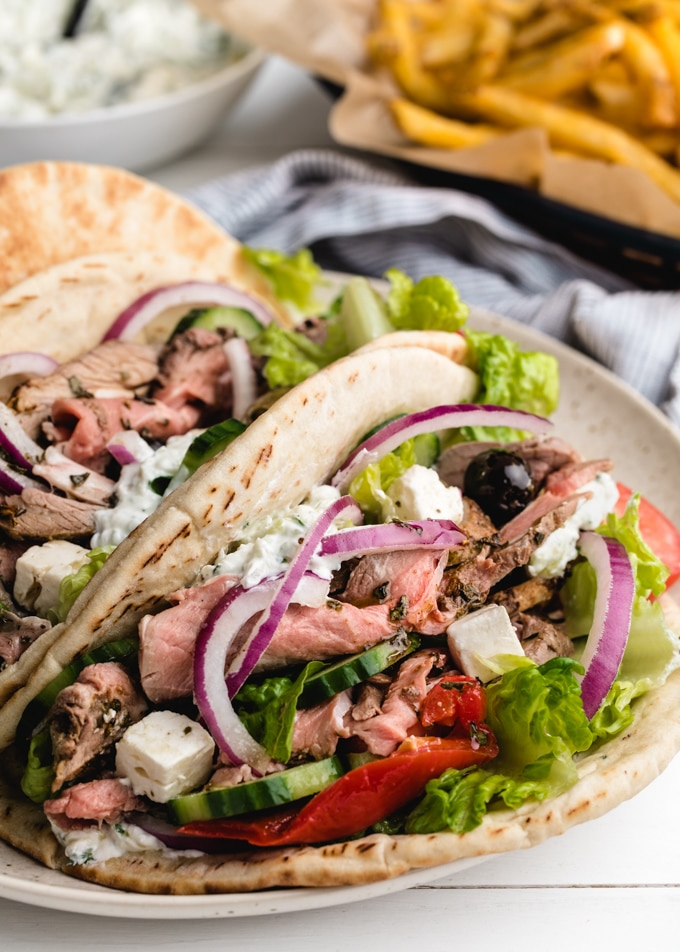 pitas stuffed with roasted lamb, tzatziki, lettuce, tomatoes, and onions