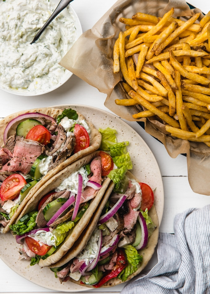 plate of loaded lamb pitas with a basket of french fries and bowl of tzatziki