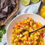 mango salsa in a bowl next to a basket of blue corn chips
