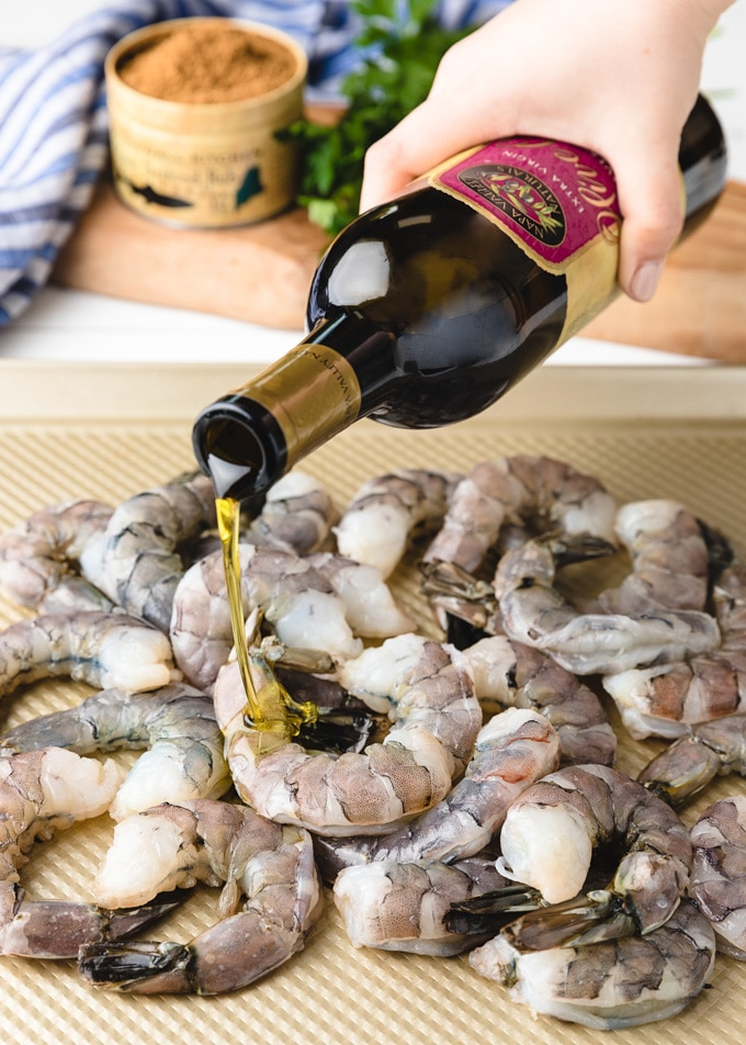 {sponsored} a bottle of Napa Valley Naturals by Stonewall Kitchen extra virgin olive oil pouring over raw shrimp