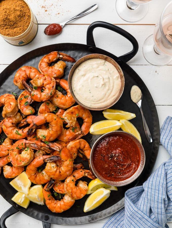 roasted shrimp cocktail with two dipping sauces on a black handled platter