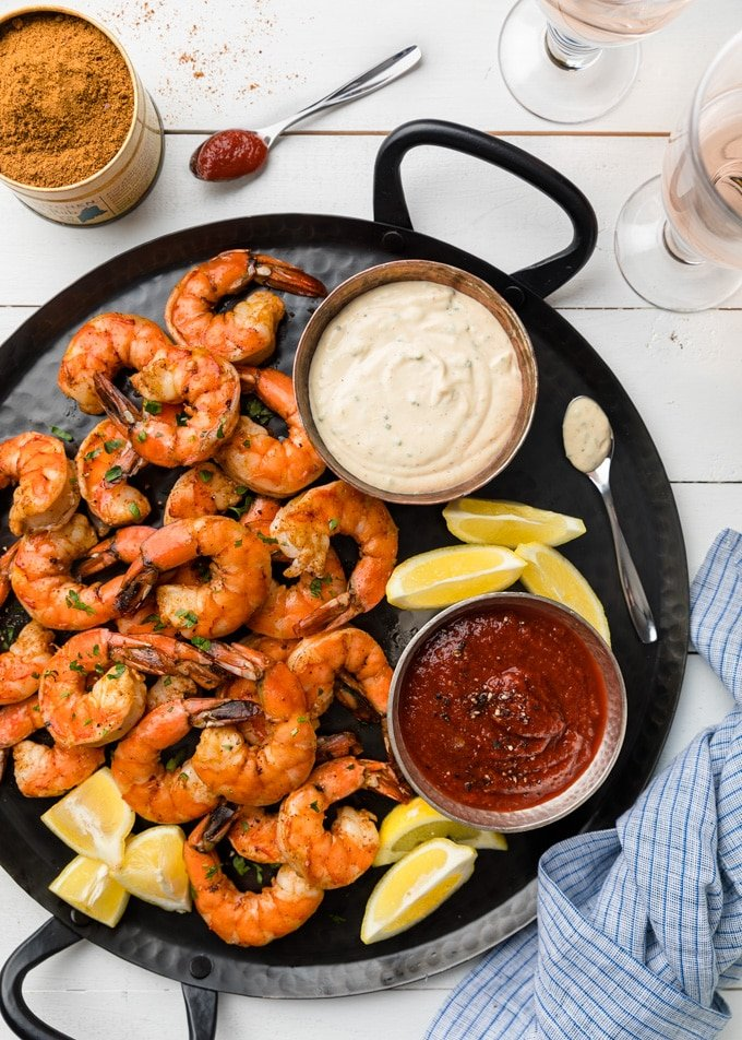 {sponsored} roasted shrimp cocktail with two dipping sauces on a black handled platter