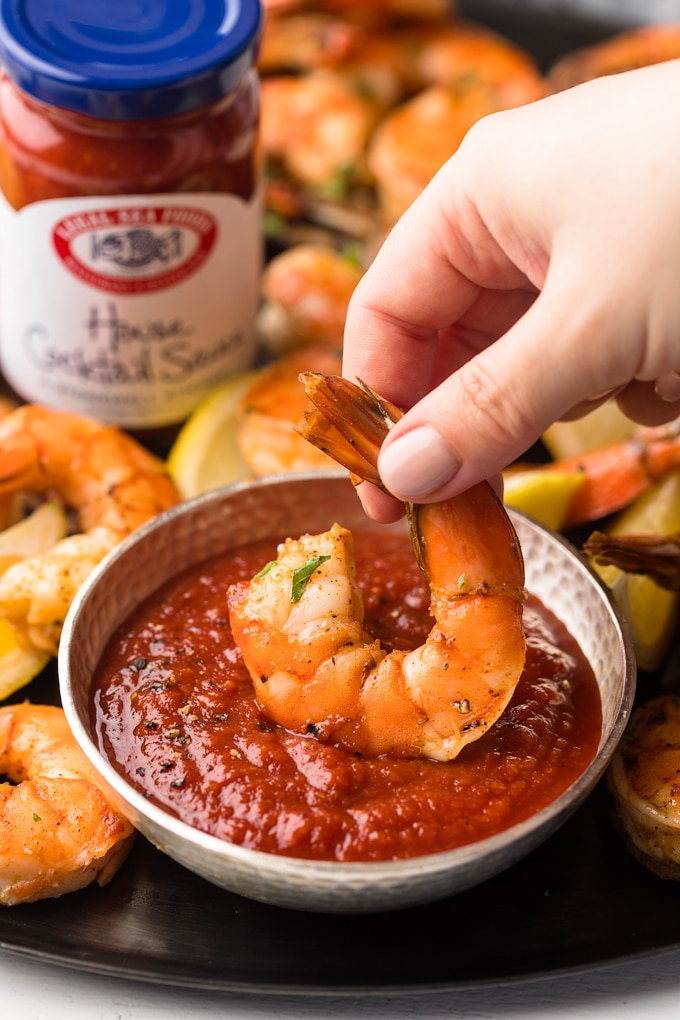 {sponsored} roasted colossal shrimp dipped into a bowl of bloody mary cocktail sauce