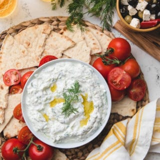 overhead of homemade tzatziki sauce in a bowl with tomatoes and torn pita bread on the side