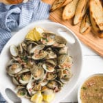 beer steamed littleneck clams in a white serving dish with a board of grilled bread slices