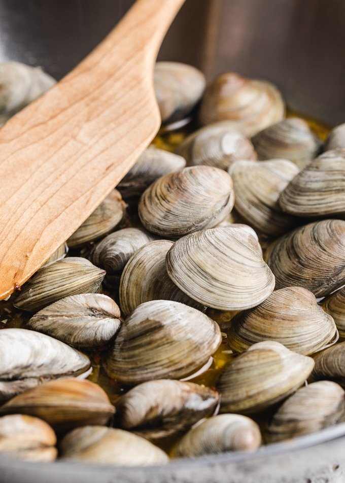 littleneck clams in a stainless steel pan with a wooden spoon
