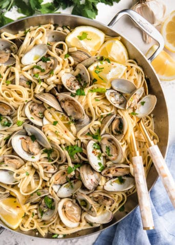 overhead of linguine with clams in a stainless steel pan