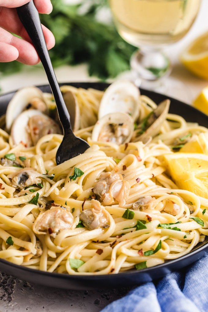 bowl of linguine with clams with a fork twirling pasta