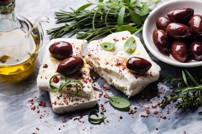 feta cheese on a board with olives, fresh herbs, and dried chili flakes