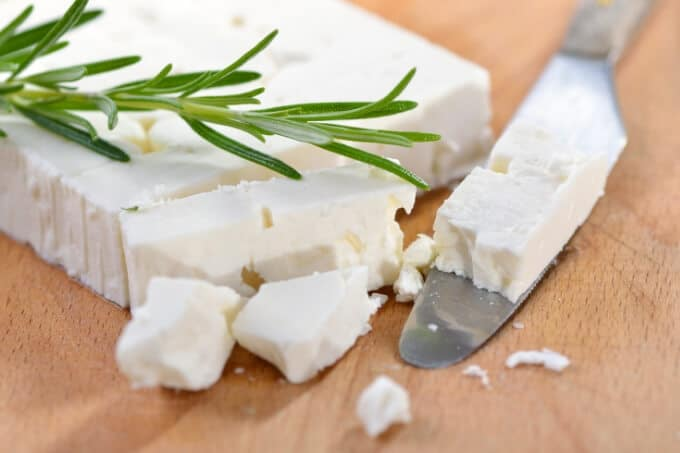 block of feta cheese on a wood board with a sprig of rosemary