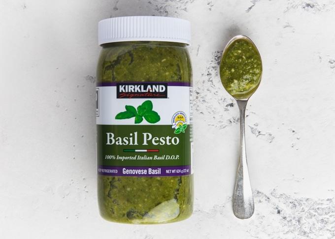 jar of kirkland basil pesto next to a spoonful of pesto