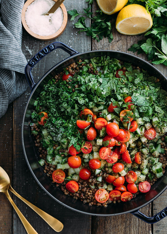cherry tomatoes, chopped herbs, and french lentils in a cast iron pot