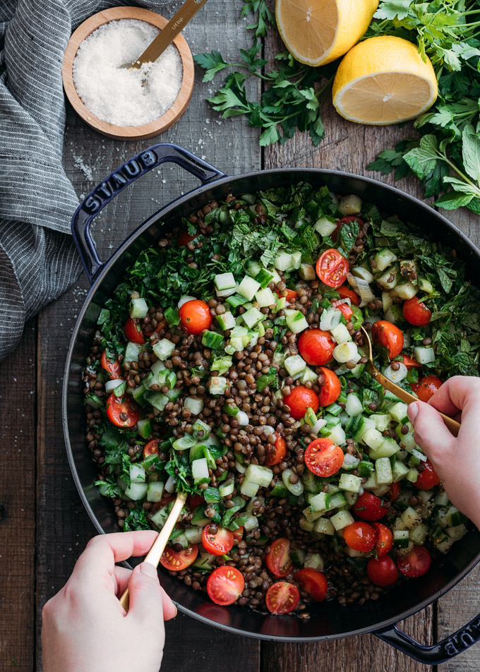 overhead photo of tossing lentil tabbouleh salad in a cast iron pan with gold colored spoons