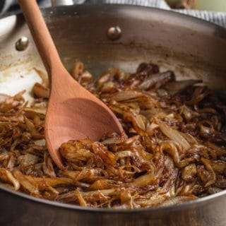 caramelized onions in a stainless steel skillet with a wooden spoon