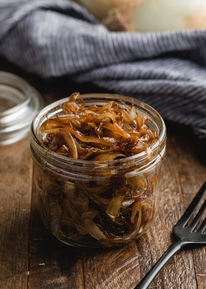 glass jar of caramelized onions on a wood board next to a black fork