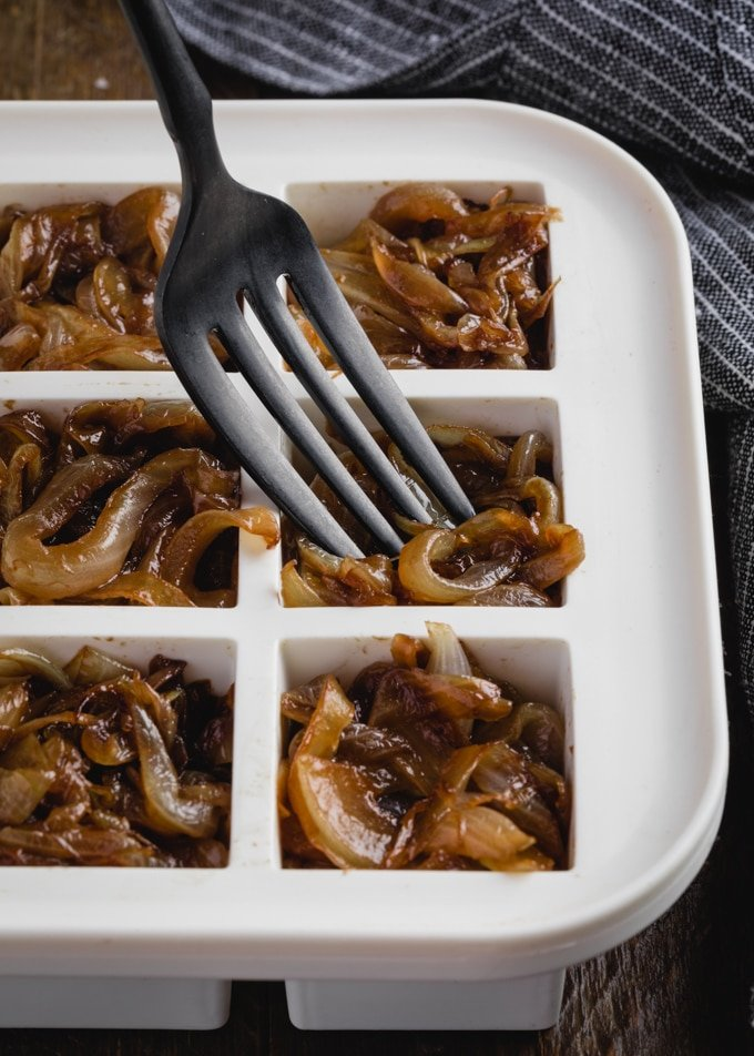fork placing caramelized onions into a white ice cube tray for freezer storage