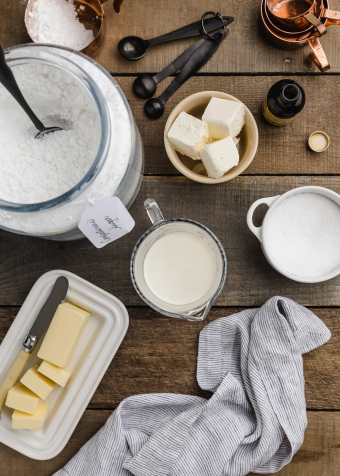 overhead view of ingredients needed for cream cheese glaze on a wood board (butter, confectioner's sugar, cream cheese, milk, salt)