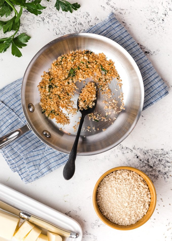 toasted panko breadcrumbs in a skillet, surrounded by butter and a bowl of un-toasted crumbs